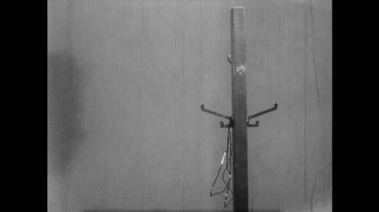 1950s: Man puts coat on hanger, touches coat rack, hangs coat on rack. Man and doctor exit room, man talks, doctor helps man put on coat.
