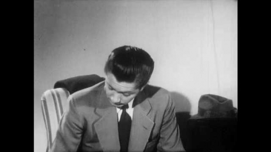 1950s: Man in suit sits in chair, talks. Man sits in chair with leg in cast up on ottoman, talks. Man picks up pencil, writes on cast.
