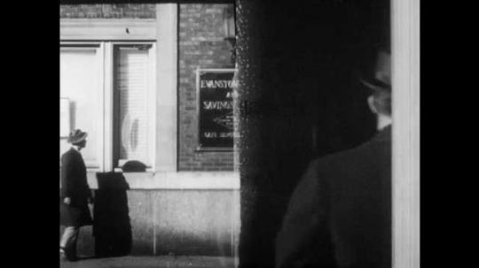 1950s: Man walks into bank. Man walks down sidewalk, stops and looks in shop window.