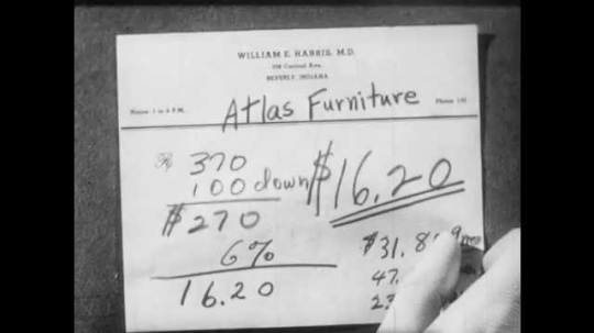 1950s: Man puts notes on finance terms on desk one at a time. Man sits at desk, thinks.