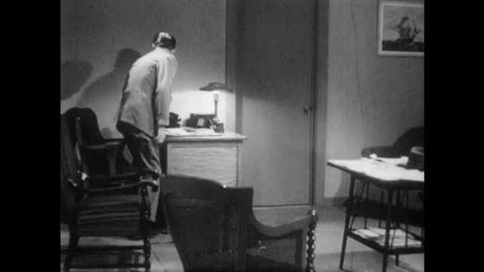 1950s: Man stands up from desk, picks up jacket, puts on hat. Doctor walks out of room, looks at waiting room, talks.