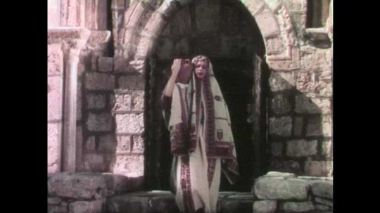 1950s: Woman in robes and head coverings carries clay pitcher down stone roads.