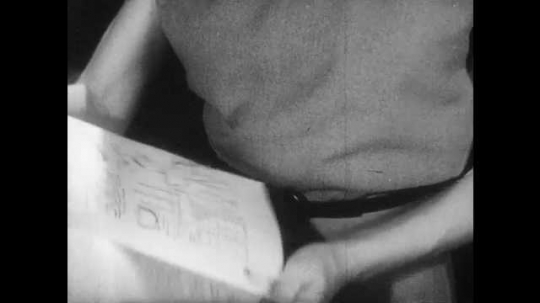 1940s: Woman holds up book, shows smudges to boy. Boy shakes head, looks at hands. Woman nods.
