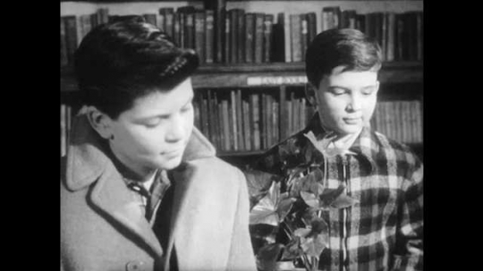 1940s: Boys look down, smile. Woman stacks books, hands stack to boy. Boys walk away, woman writes on card on desk.