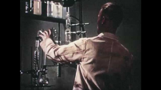 1940s: Man pours chemical from glass into science equipment. Glass full of liquid. Drawing of molecules.