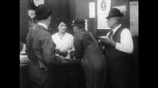 1910s: Man struggles against two other men. Woman leans in and points at struggling man, man bows and walks off. One of the other men turns and talks to woman behind desk.