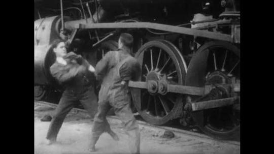 1910s: Men in fist fight. Other men and woman come up and break up fight. Man yells in other man