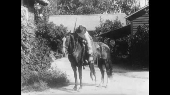 1910s: Woman on horse grabs dog, then gallops away. Man waves at other man, who enters train. Train begins to move. Man looks around, then jumps on train.