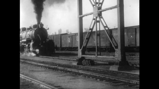 1910s: Train moves on track, smoke comes out of smokestack. Woman rides horse as dog follows. Woman dismounts and pulls reins over horse