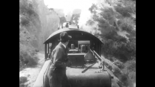 1910s: Man on train looks back, then runs to front. Boy on push cart stops moving, heads into train station. He hands another boy piece of paper, then points at it. Woman reads paper. Boys talk.