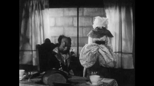 1940s: Man puppet sits at table, looks grumpy, woman puppet looks out window, they talk. Man gets up from table, woman turns to man, they talk. Man walks away, woman follows.
