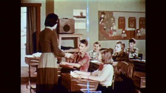 1950s: Teacher hands book to boy at front desks of classroom, speaks to students. Students pass art supplies to each other along rows.