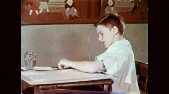1950s: Boy at classroom desk prepares to paint with brush, water, paints, and paper. Fingers smooth wet paintbrush bristles. Boy dips water onto each paint in his palette.