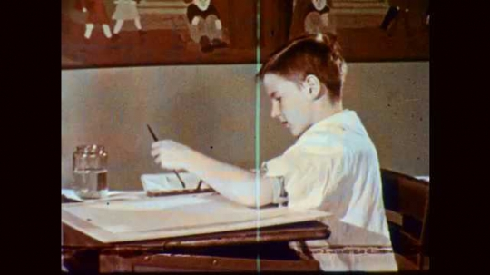 1950s: Girl at classroom desk flips through book of painted illustrations. Painting of farmland on book page. Girl puts book in desk and gets ready to paint.