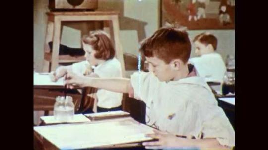 1950s: Students paint at desks, boy in front swirls water around paper.