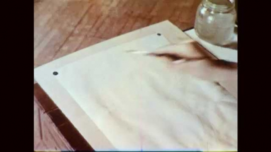 1950s: Hand washes blue watercolor paint onto paper on desk with brush.
