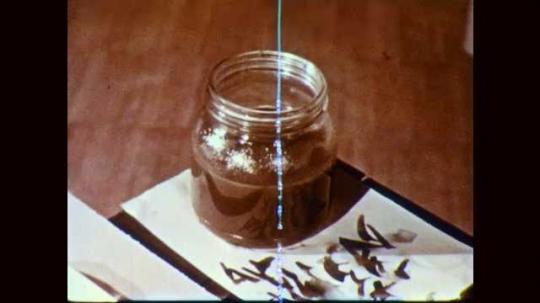 1950s: Dirty paint jar on desk. Boy dumps paint in classroom bucket, refills water jar, sits down at desk.