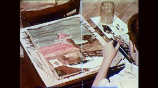 1950s: Boy paints house on paper at school desk. Girl paints at desk, sits back. Painting of book cover on desk.