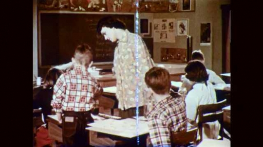 1950s: Teacher looks at paintings on desks of art students. Girl washes brush in water, dips in paint.