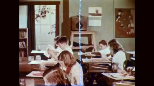 1950s: Students clean supplies at art class desks. Students bring paintings to front table. Paintings on table.