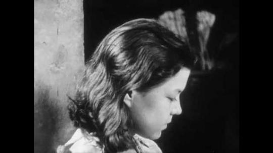 1940s: Girl looks up, boy reads aloud. Woman walks through garden with bouquet of flowers. Men duel under oak tree outside.