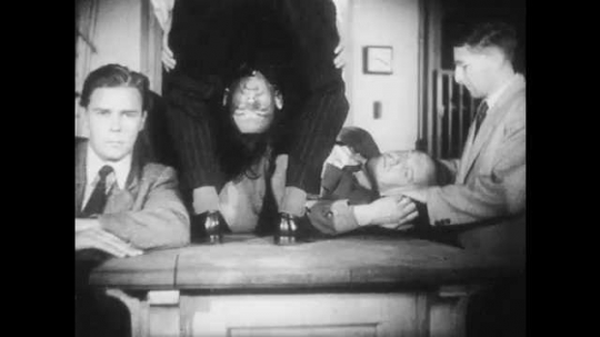 1950s: A man sits, a man lays on table, a man has his head between his legs, another man adjusts their positions. A man stands three times repeated. Hand puts glasses on the head of the man who sits.