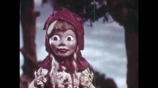 1940s: Animation of Little Red Riding Hood, she looks around in the forest, smiles, remembers her mother?? advice. Little Red Riding Hood walks off the path towards a river and looks at flowers.