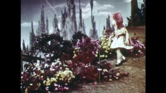 1940s: Animation of Little Red Riding Hood in the forest, she admires flowers and picks them. Little Red Riding Hood collects flowers, walks towards the river and sits on the ground by the river.
