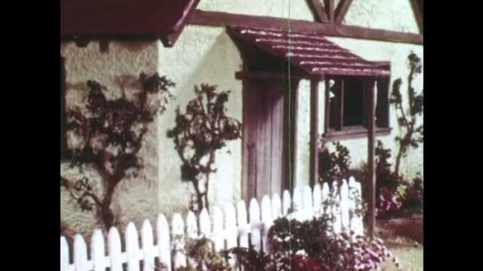 1940s: Animation of house, view through the window of grandmother who sleeps. Wolf stands at front door. Grandmother sleeps in bed. Door opens, wolf stands in door frame and shows its teeth.