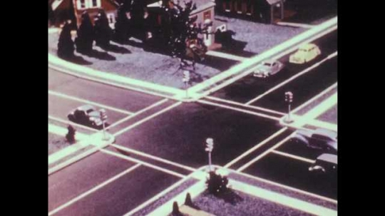 1940s: Model cars drive through four-way intersection. Cars drive down two-way, three lane roads.