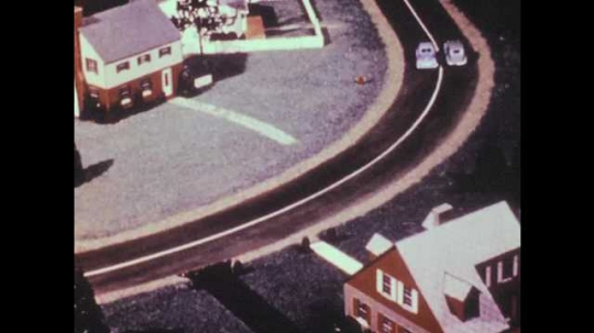 1940s: Model cars drive around bend. Car drives down center of two-lanes. Cars drive through intersection.