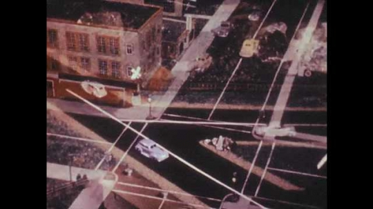 1940s: Model cars drive through T intersection and stop at train tracks before crossing.