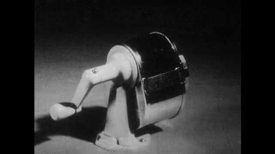 1950s: UNITED STATES: wheel on pencil sharpener. Spoke on wheel. Handle on sharpener. Model of windlass.