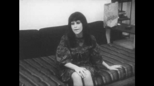 1960s: woman in dress with black hair sits on daybed, talks, listens, smiles and rubs hands on legs in living room with paper grocery bag on end table.