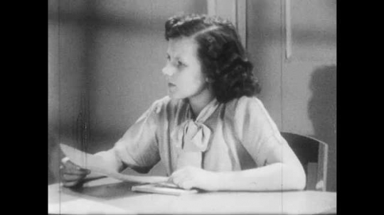 1950s: Girl holds paper, talks, puts paper on desk. Girl places hand on letter, then on blank sheet of paper. Boy stands and talks on telephone.