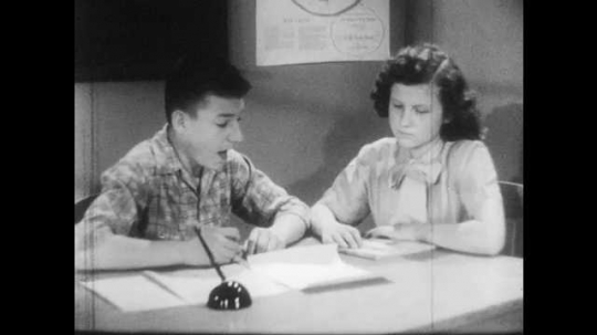 1950s: Boy and girl sit at desk, look at paper, talk.