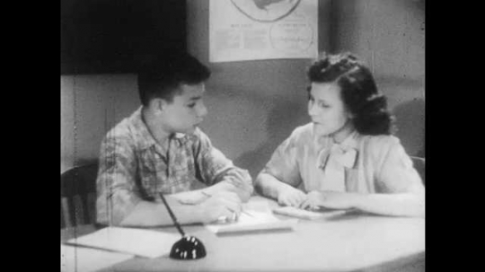 1950s: Boy and girl sit at desk, look at paper, talk. Teacher sits at desk. Students work in group at desk.