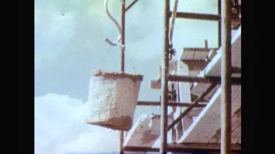 1960s: Bucket with cement goes up, construction worker takes bucket. Man and boy walk around house construction site.