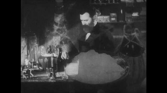 1930s: 1860s reenactment. A bearded man holds up a test tube and looks through. He puts a drop of liquid on a slide and looks at it under a microscope.