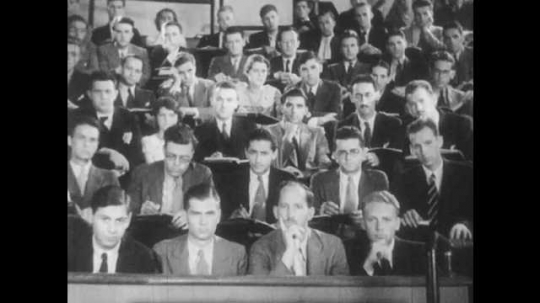 1930s: Students sit in a lecture hall. They listen and take notes. A man lectures at the front of the room. A microscope turns on its side. Microscope lens.