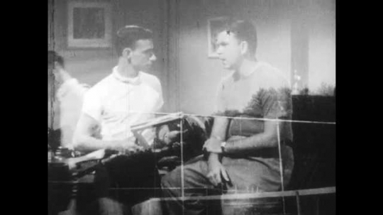 1950s: Boy talks to coach holding a tennis racket. Coach talks and holds racket.
