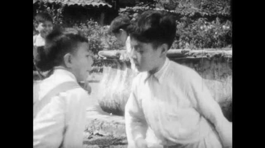 1930s: Boys hop on one foot and bump into each other.  Boys try to catch spool on stick.