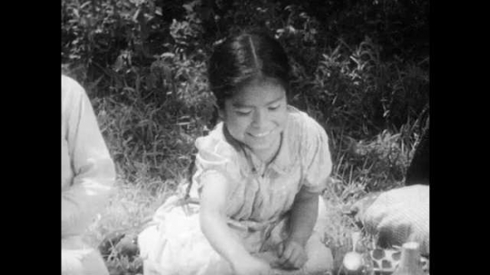 1930s: Girl rolls tortilla and dips into bowl.  Children eat.  Mother and baby.  Father pours water and drinks.