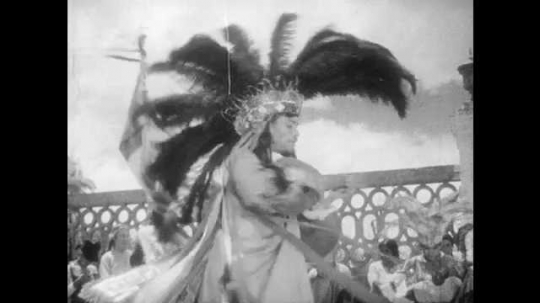 1930s: Men play guitar and dance in ceremonial costumes.  Crowd watches.