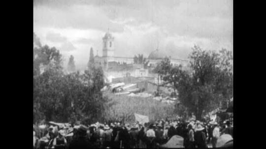 1930s: Crowd of people in village.  Family travels across field.  People ride donkeys.  Sunset.