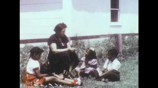 1950s: Mother and children sit on lawn with puppy. Children lift and pet puppy. Girl scratches puppy