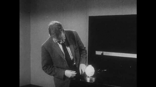 1960s: UNITED STATES: object moves across table. Man picks up piece of foil. Man speaks to camera