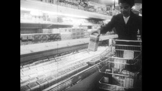 1950s: Woman places cartons of milk into grocery cart. Dairy truck pulls up in front of house, milkman gets out.