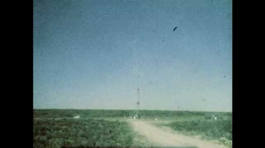 1980s: UNITED STATES: view across land towards mine site. Blue sky. Green fields. Buildings at mine