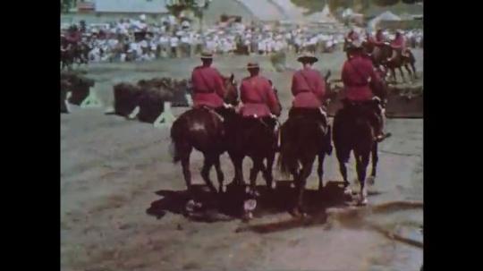 1960s: Policemen perform on horseback at exhibition.  Men put saddle on horse.